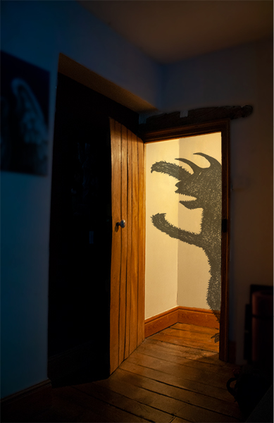 photograph of horned beast creeping around lit doorway